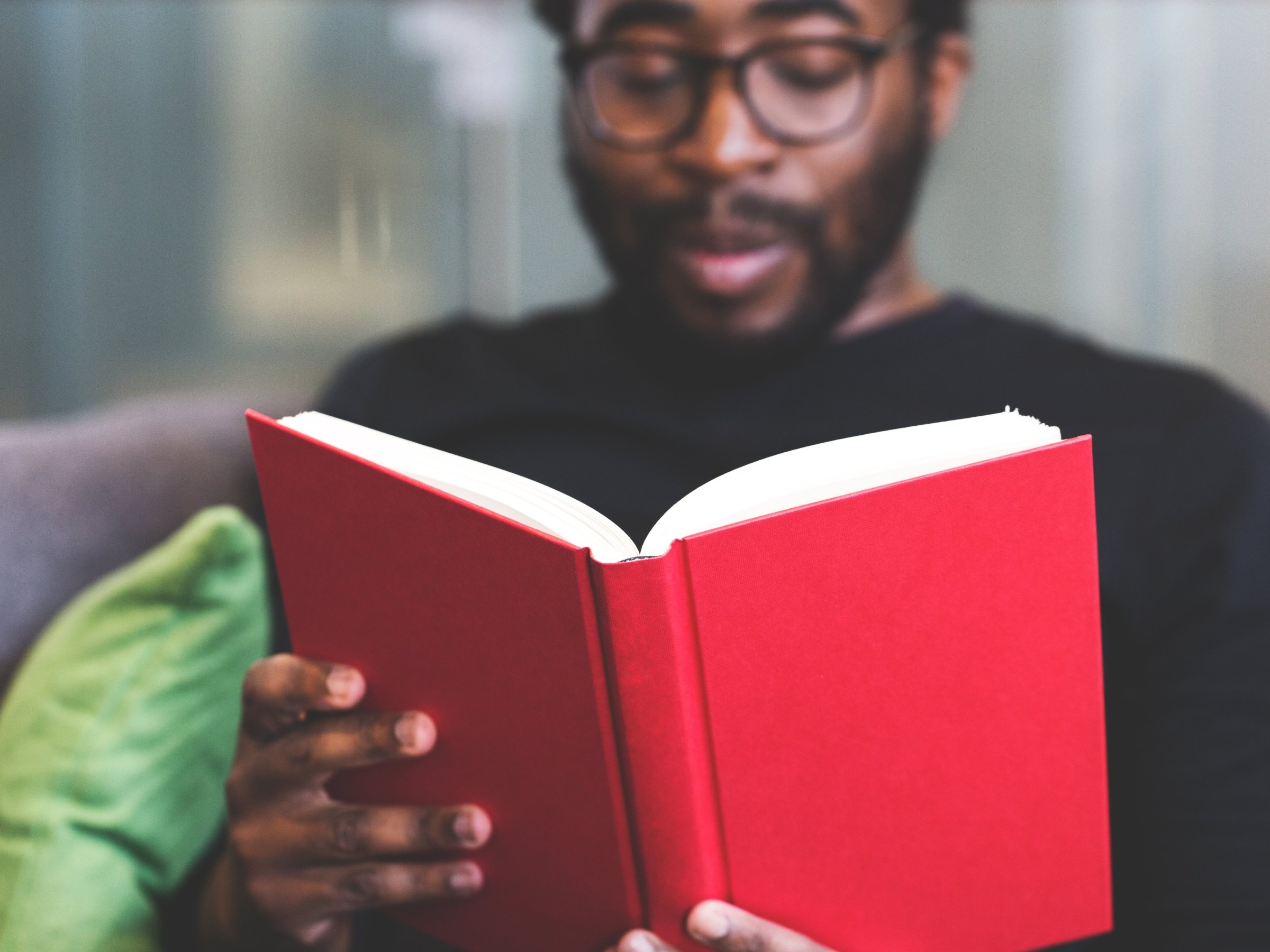 Black man with a beard and glasses sitting on a couch reading a red book