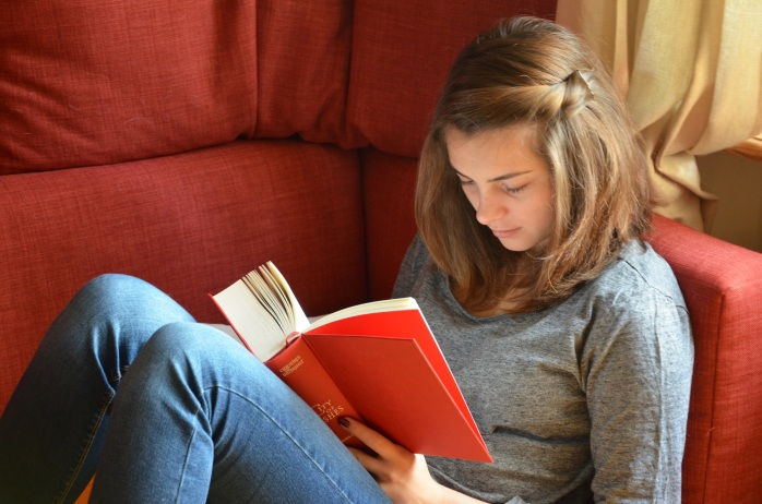 Teenage white girl with brown hair reading a red book on a couch